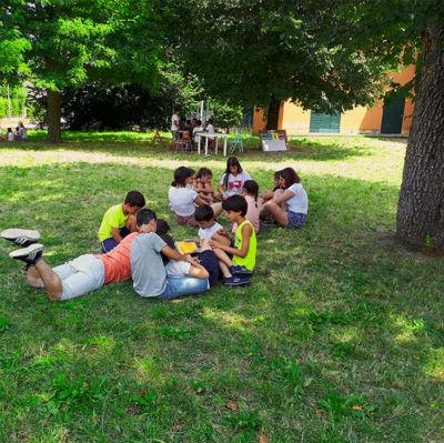 centro estivo di inglese bambini seduti sull'erba fano